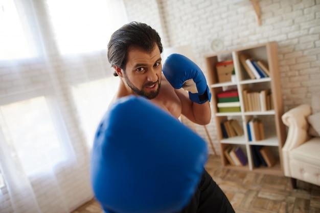 O homem atlético considerável em luvas de encaixotamento faz o perfurador.