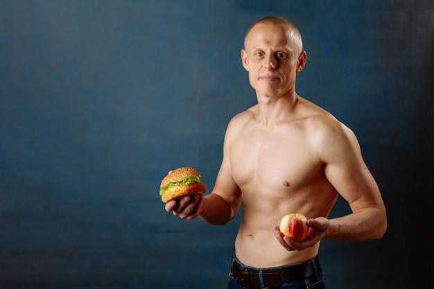 O homem atlético muscular forte novo segura a maçã e o hamburguer saudável do fast food da sucata. o conceito de escolher a comida certa
