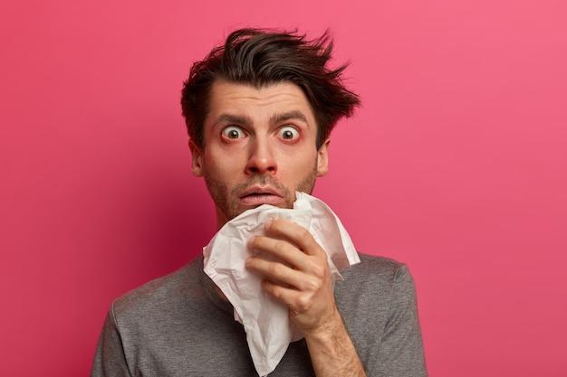O homem atordoado e doente tem gripe, vírus ou alergia respiratória, olhos vermelhos lacrimejantes, assoa o nariz em um lenço de papel, descobre doenças graves, posa sobre uma parede rosa. conceito de saúde, medicina e sintomas