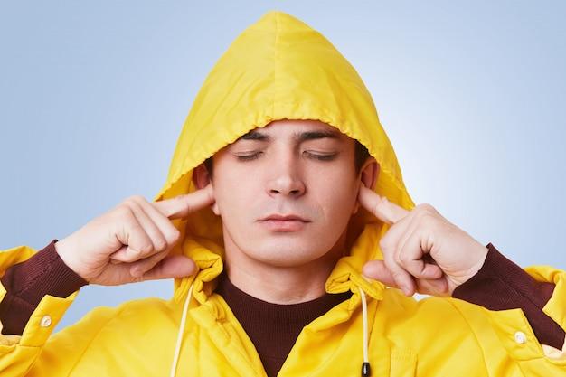 O homem atraente repousante fecha os olhos e liga os ouvidos, tenta se concentrar e não ouve barulho alto, usa capuz amarelo na cabeça