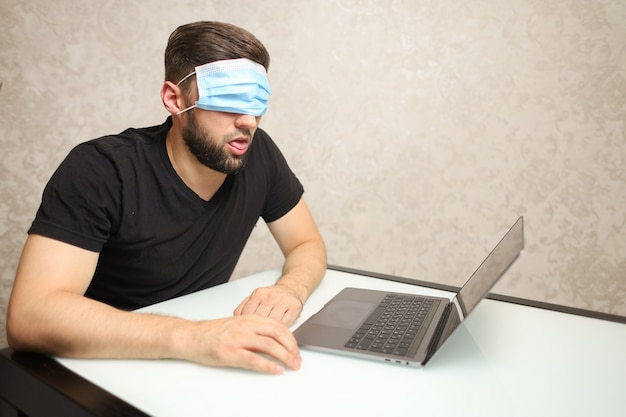 O homem atrás do laptop colocou uma máscara médica sobre os olhos