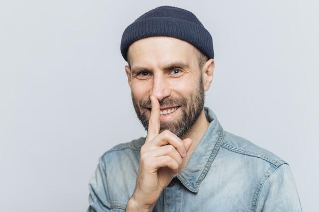 O homem atrativo alegre com olhos azuis mostra o sinal do silêncio, satisfez a expressão