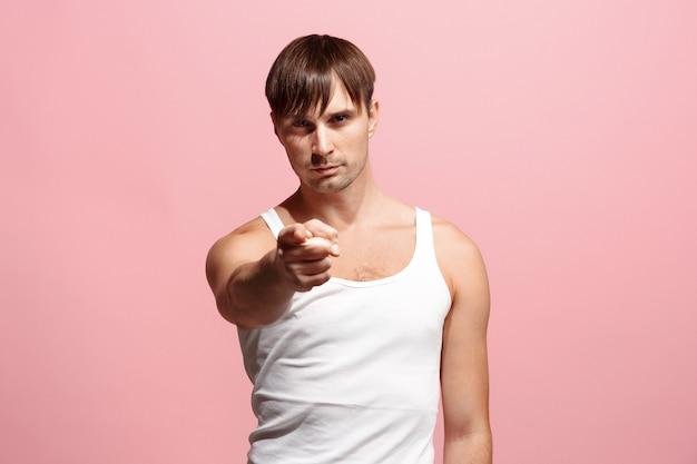 O homem autoritário apontá-lo e quero você, retrato de meio comprimento closeup no espaço rosa.
