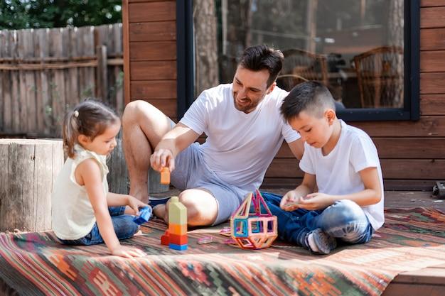 O homem babá brinca com duas crianças, sentado na varanda perto de uma casa de madeira no campo, passa o tempo livre ajudando crianças a coletar cubos de brinquedo