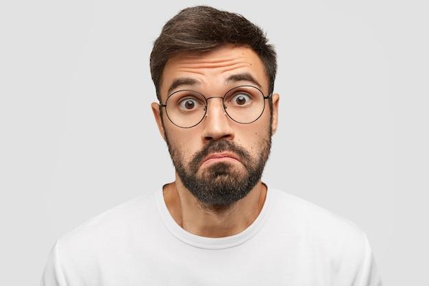 O homem barbudo duvidoso franze os lábios em hesitação, encara a câmera com uma expressão assustada,