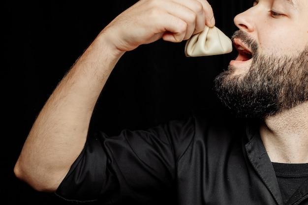 O homem barbudo está comendo khinkali