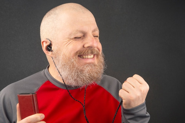 O homem barbudo gosta de ouvir sua música favorita em um reprodutor de áudio em pequenos fones de ouvido. audiófilo e amante da música. música e som hi-fi.