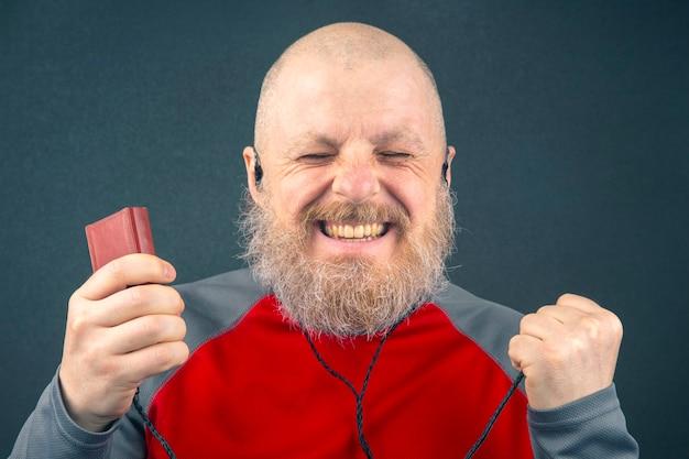 O homem barbudo gosta de ouvir sua música favorita em um reprodutor de áudio em pequenos fones de ouvido.