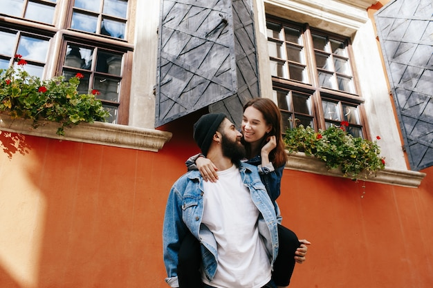 O homem barbudo segura uma senhora sorridente nas costas de pé diante de grandes janelas com flores