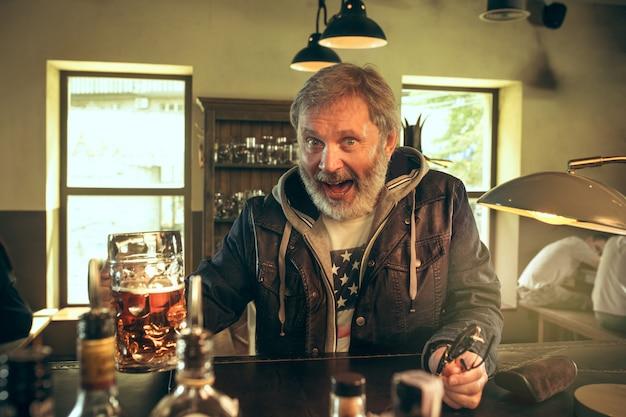 O homem barbudo sênior bebendo cerveja no pub