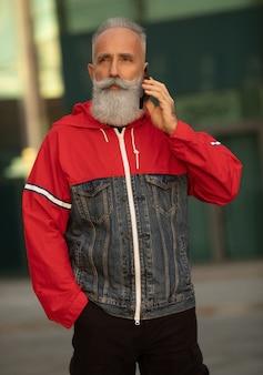 O homem barbudo sênior bonito está falando por um smartphone enquanto toma café em uma rua ao lado do prédio de escritórios.