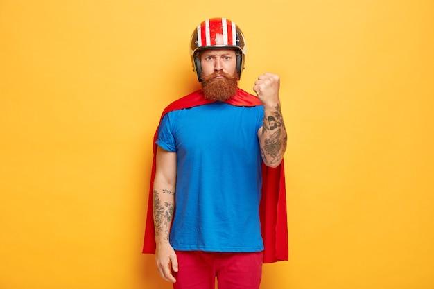 O homem barbudo sério aperta os punhos, mostra força, pronto para vingar o mal pelas coisas ruins