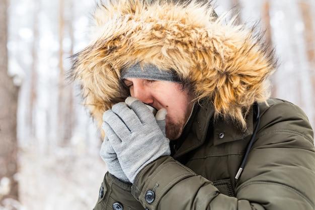 O homem bebe uma bebida quente de uma garrafa térmica e aproveita a natureza no inverno.