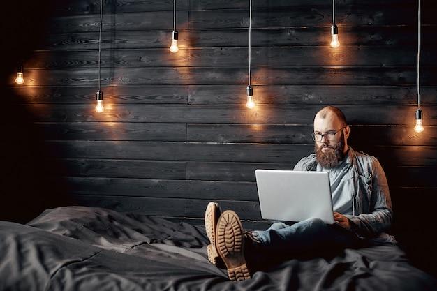 O homem bem sucedido do freelancer do estilo de vida com barba consegue o objetivo novo com o portátil no interior do sótão