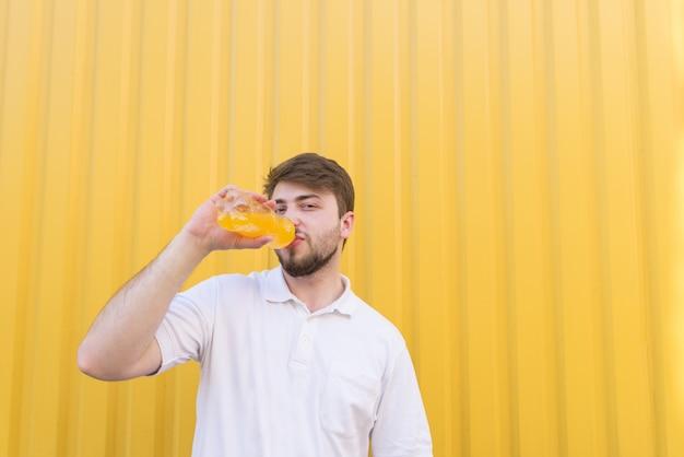 O homem bonito com uma barba bebe suco de uma garrafa em uma parede amarela.