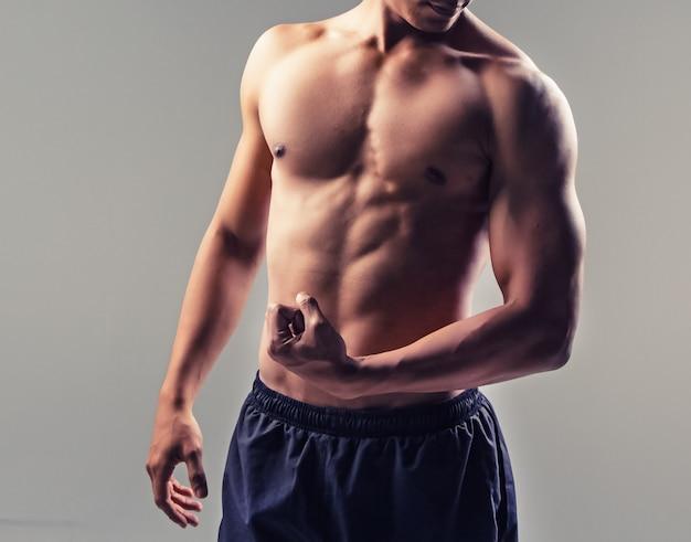 O homem bonito mostra corpo em forma e firme, músculos fortes, tons vintage e art