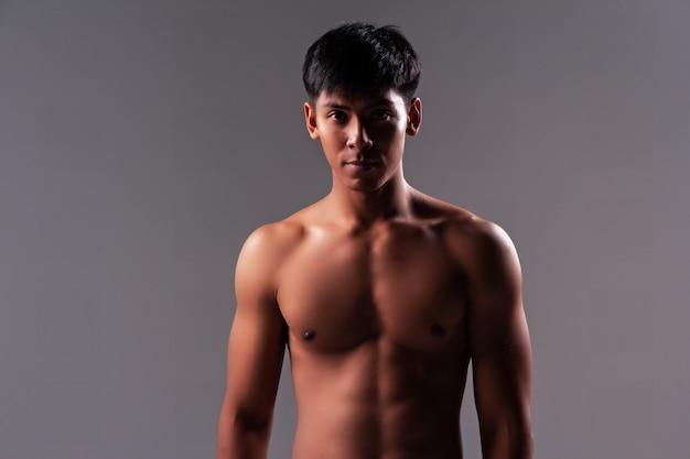 O homem bonito mostra o músculo do corpo