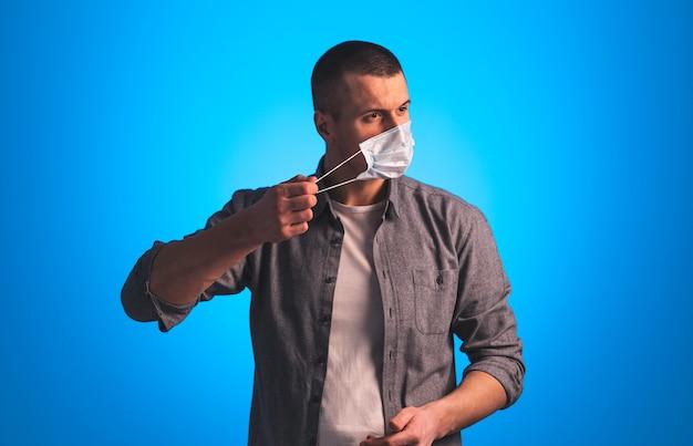 O homem bonito tira uma máscara médica protetora