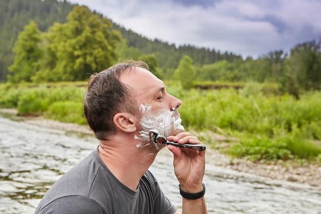 O homem branco está barbeando o rosto com ajuda de navalha e espuma de barbear na natureza durante suas férias.