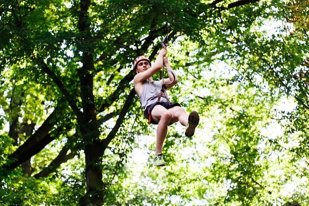 O homem cai na corda em um parque de entretenimento