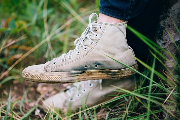 O homem caminhante com bastões de trekking sobe íngreme na trilha de montanha, foco na bota.