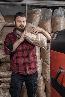 O homem carrega as pelotas na caldeira de combustível sólido, trabalhando com biocombustíveis, aquecimento econômico.