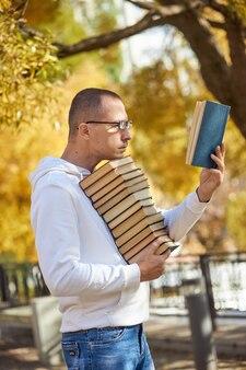 O homem carrega muitos livros nas mãos