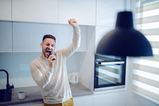 O homem caucasiano bonito brincalhão vestiu-se ocasional, ouvindo sua música favorita por telefone inteligente e fingindo cantar no microfone. interior da cozinha doméstica moderna.