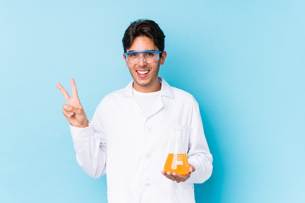O homem caucasiano cientific novo isolou alegre e despreocupado mostrando um símbolo de paz com os dedos.