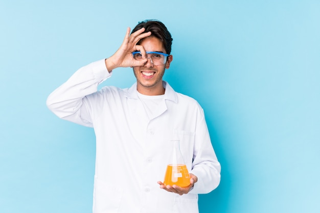 O homem caucasiano cientific novo isolou entusiasmado mantendo o gesto aprovado no olho.