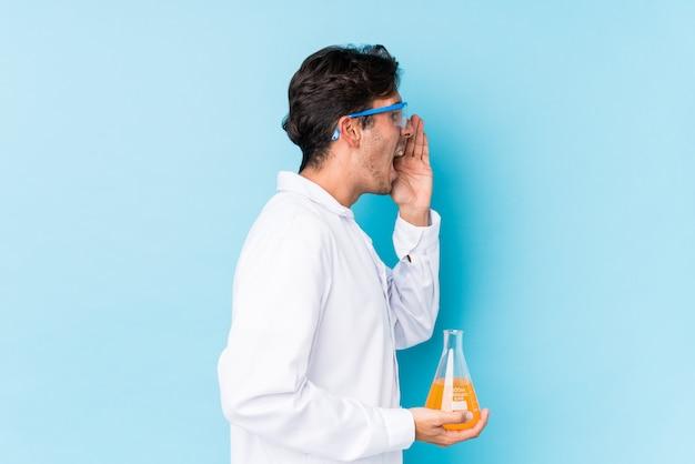 O homem caucasiano científico novo isolou a gritaria e que guarda a palma perto da boca aberta.