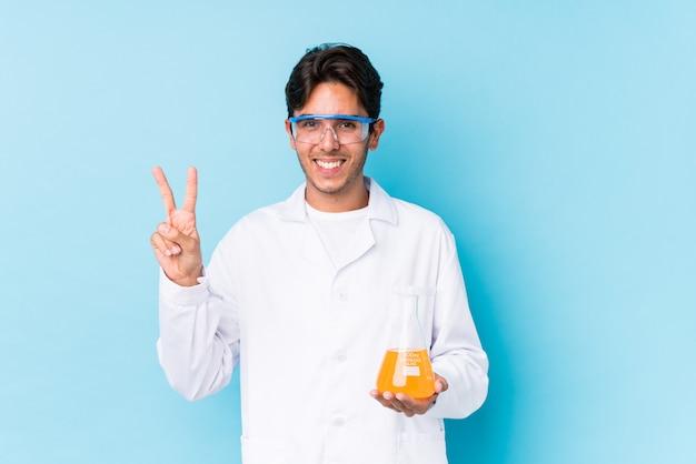 O homem caucasiano científico novo isolou mostrar o número dois com dedos.