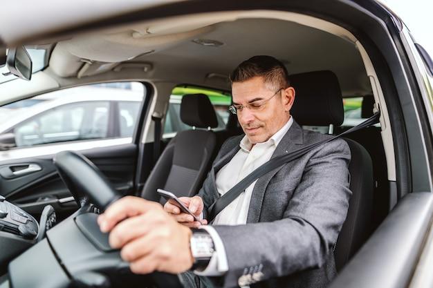 O homem caucasiano de sorriso vestiu ocasional esperto com cinto de segurança e com a mão no volante que processa o telefone esperto para escrever ou ler a mensagem. interior do carro.
