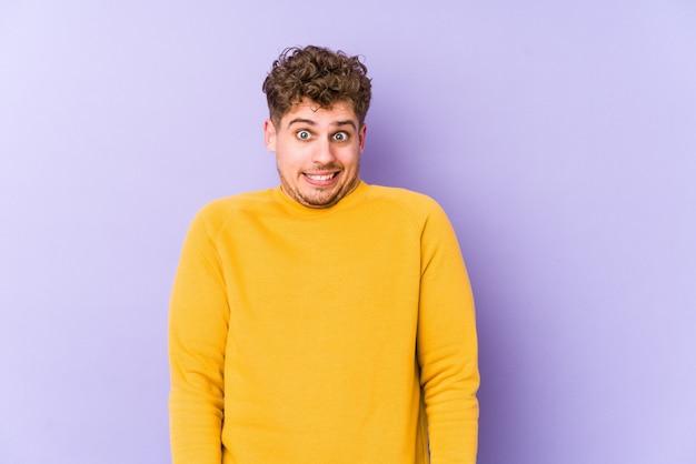 O homem caucasiano do cabelo encaracolado louro novo isolado funde as bochechas, tem expressão cansada. conceito de expressão facial. Foto Premium