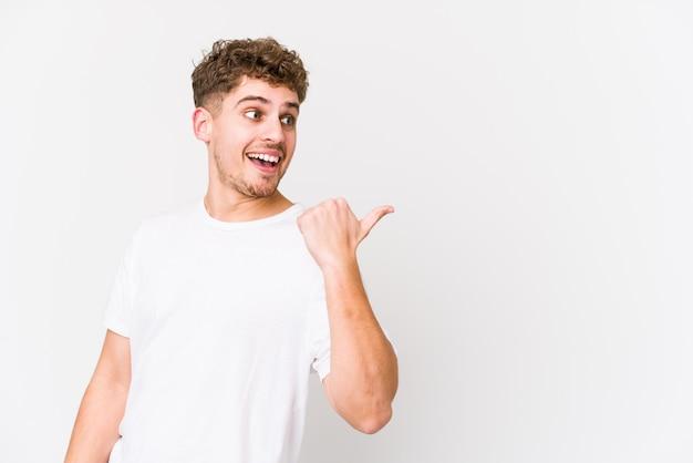 O homem caucasiano do cabelo encaracolado louro novo isolou pontos com o dedo do polegar afastado, rindo e despreocupado.