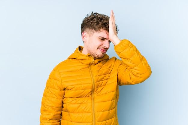 O homem caucasiano do cabelo encaracolado louro novo isolou-se esquecendo algo, batendo na testa com palma e fechando os olhos.