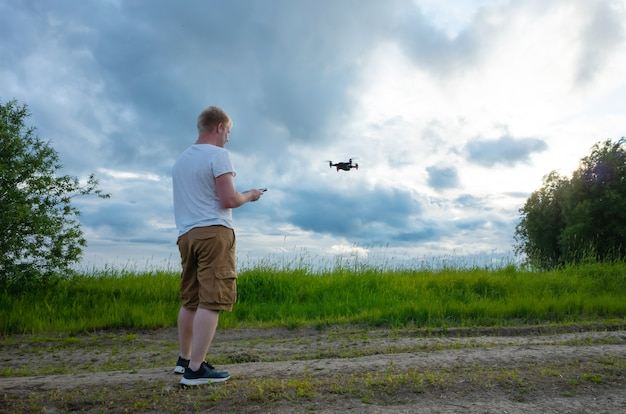 O homem caucasiano em um t-shirt e no short brancos controla um quadrocopter em um esclarecimento com grama e árvores.