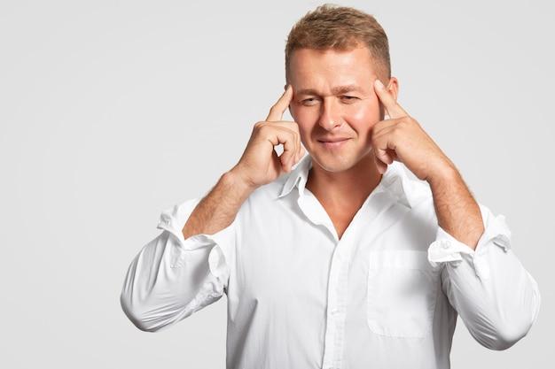 O homem caucasiano novo com expressão facial concntrated mantém os dedos dianteiros nos templos, focalizados para baixo, pensa em algo, tenta recordar a informação necessária, isolada na parede branca.