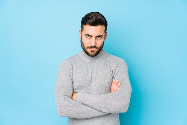 O homem caucasiano novo contra um fundo azul a cara olhando de sobrancelhas franzidas isolado no descontentamento, mantém os braços dobrados.