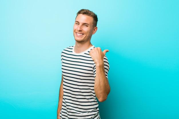 O homem caucasiano novo contra uma parede azul aponta com o dedo do polegar afastado, rindo e despreocupado.