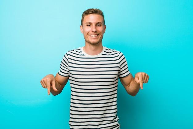 O homem caucasiano novo contra uma parede azul aponta para baixo com os dedos, sentimento positivo.