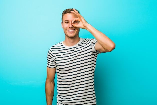 O homem caucasiano novo contra uma parede azul excitou mantendo o gesto aprovado no olho.