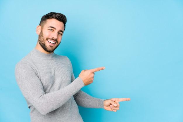 O homem caucasiano novo contra uma parede azul isolou apontar entusiasmado com os dedos indicadores ausentes.