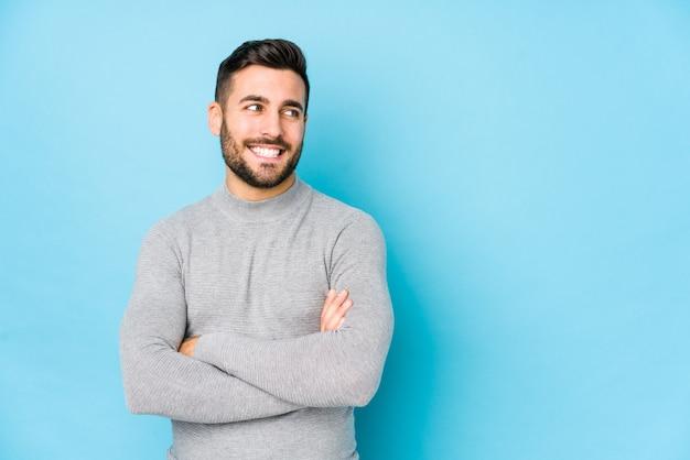 O homem caucasiano novo contra uma parede azul isolou o sorriso seguro com braços cruzados.
