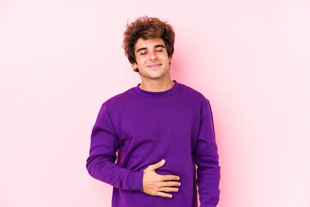 O homem caucasiano novo contra uma parede cor-de-rosa isolada toca na barriga, sorri delicadamente, comendo e conceito da satisfação.