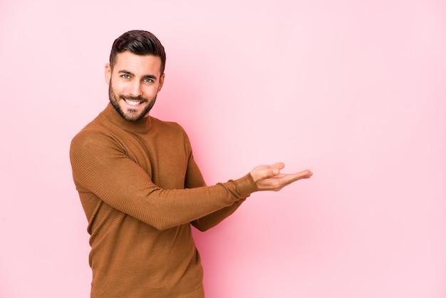 O homem caucasiano novo contra uma parede cor-de-rosa isolou guardar um espaço da cópia em uma palma.