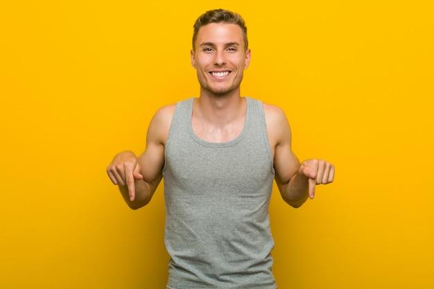 O homem caucasiano novo do esporte aponta para baixo com os dedos, sentimento positivo.