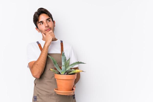 O homem caucasiano novo do jardineiro que guarda uma planta isolou a vista lateralmente com expressão duvidosa e cética.