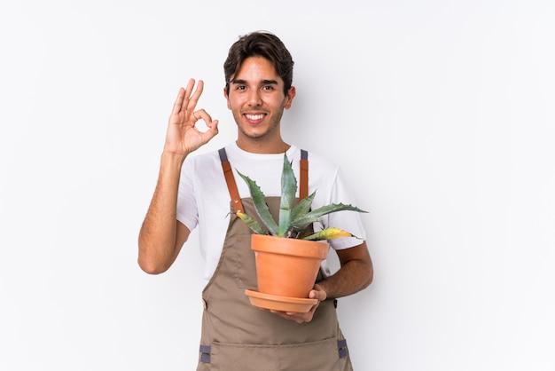 O homem caucasiano novo do jardineiro que guarda uma planta isolou o gesto alegre e seguro aprovado da exibição.