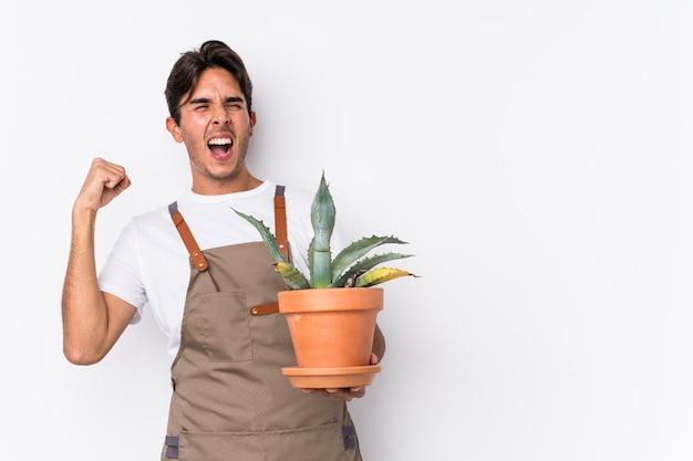 O homem caucasiano novo do jardineiro que guarda uma planta isolou o punho de levantamento após uma vitória, conceito do vencedor.